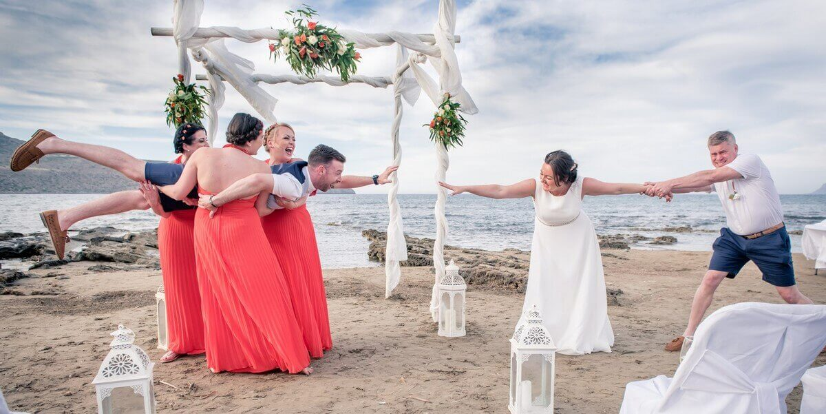 Bridesmaids lift groom at Crete beach wedding