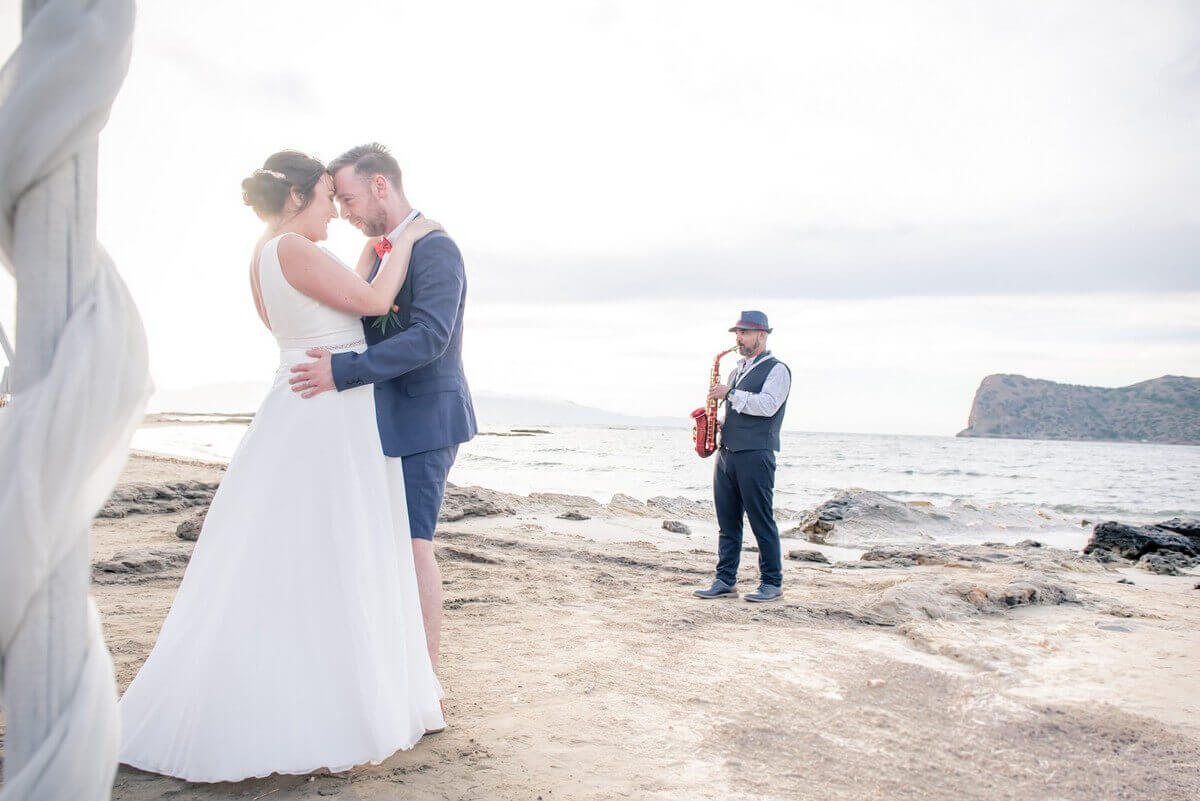 bride and groom hug with sax player in the background at a Crete beach wedding