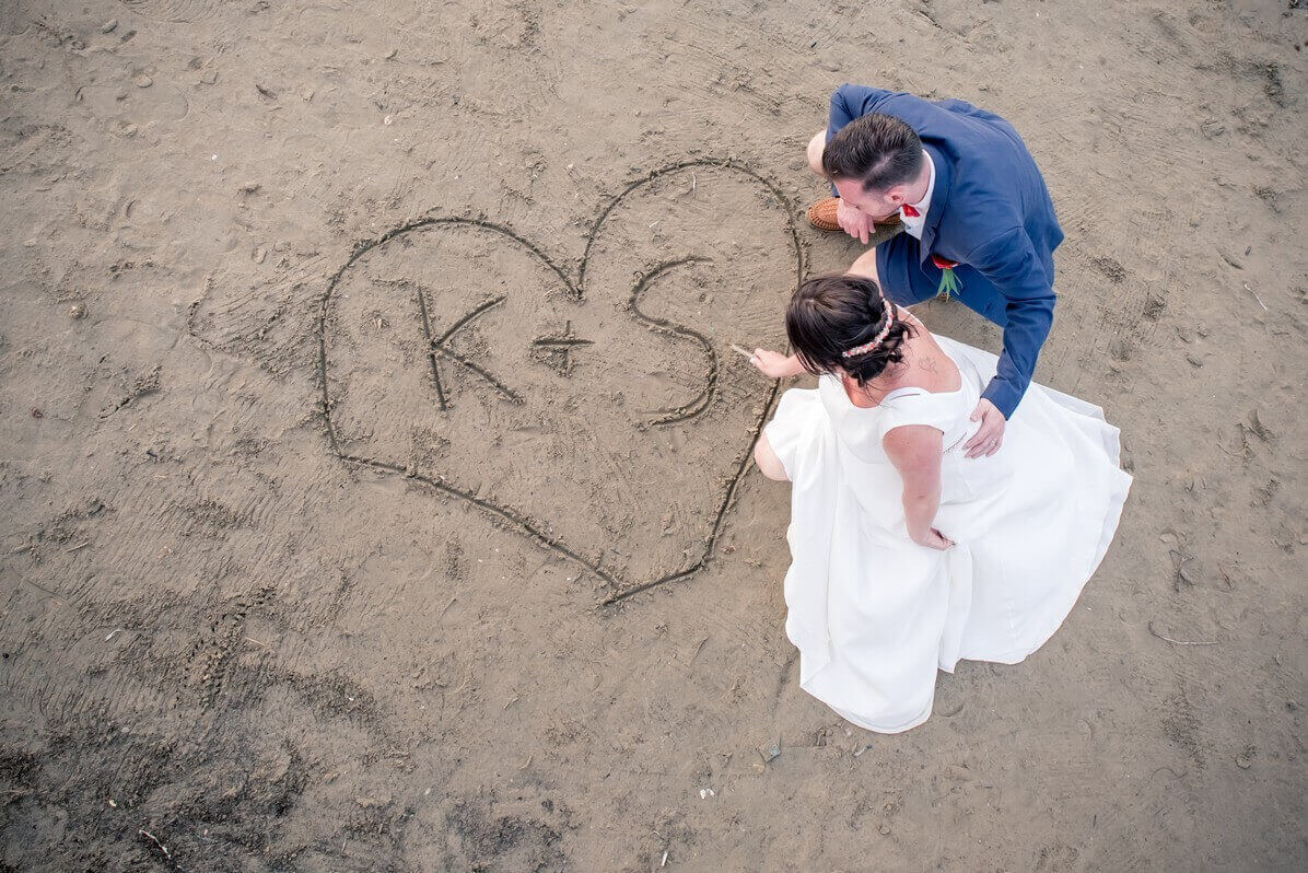 Bride and groom draw a heart in hte sand at their Crete beach wedding
